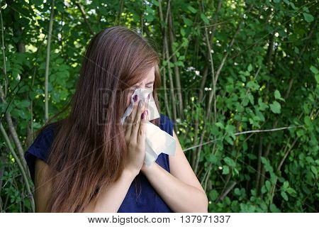 young woman blowing her nose with paper tissue