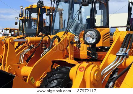 Bulldozer headlight, row of huge orange powerful construction machines, tractors, excavators, focused on spotlight, heavy industry, blue sky and white clouds on background