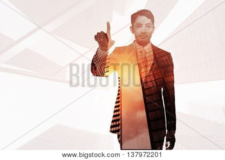 Stern asian businessman pointing against skyscraper