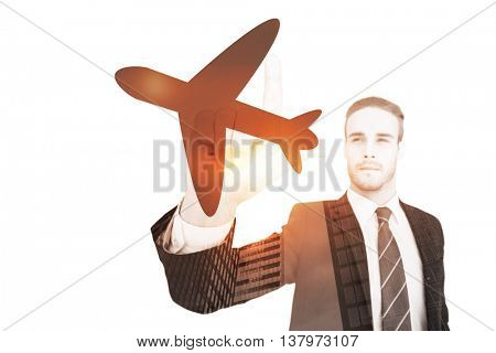Unsmiling businessman in suit pointing up his finger against airplane