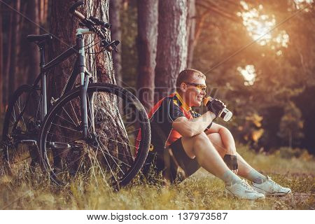 Happy man cyclist rides in the forest on a mountain bike. Adventure travel.