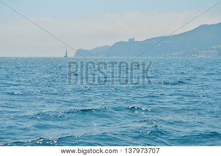 Detailed sea water surface and waves stretch out to the horizon where islands are visible far away in sunny morning.