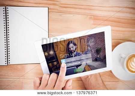Login screen superimposed on hipster man with laptop against hands holding blank screen tablet