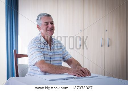 Blind man reading a braille book at home
