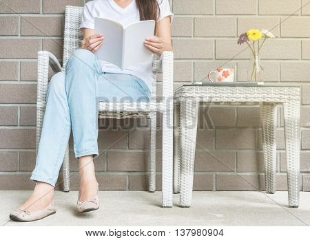 Woman sitting on wood weave chair in house for reading a white book in free time in the afternoon relax time and lifestyle of asian woman concept