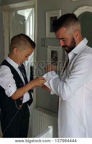 A young boy dressing his father on his wedding day as part of his best man duties