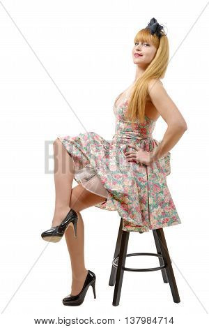Young woman in retro floral dress sitting on stool isolated on white background