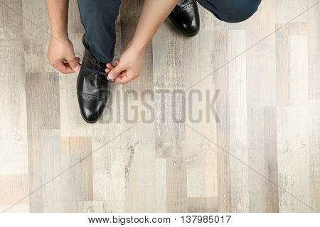 Man tying shoes laces on wooden parquet background