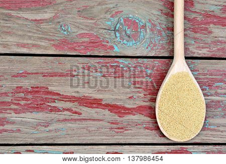Amaranth seeds in spoon on wooden background