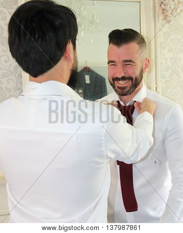 2ND JULY 2016, PORTSMOUTH,ENGLAND: A bestman helping the groom get dressed for his wedding in portsmouth, england, 2nd july 2016