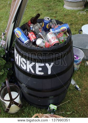 2ND JULY 2016,PORTSMOUTH,ENGLAND: The left overs of beer cans and wine bottles in an old vintage beer barrel after a party in Portsmouth, England, 2nd july 2016
