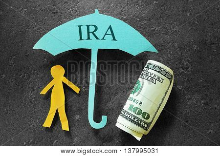 Paper person under an IRA umbrella with cash