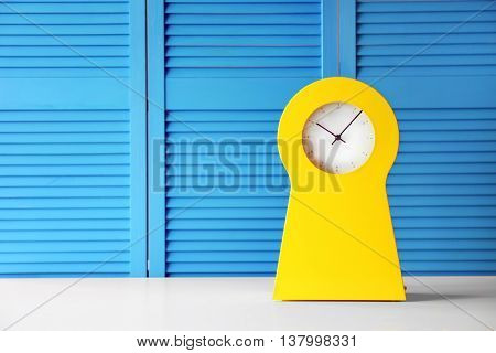 Stylish clock on blue folding screen background