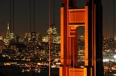 A shot of the famous landmark Golden Gate Bridge with San Francisco city lights in the background. poster