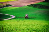 Farm machinery spraying insecticide to the green field, agricultural natural seasonal spring background, vintag retro hipster style poster