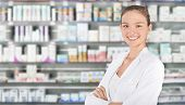 Young female smiling pharmacist standing in pharmacy poster
