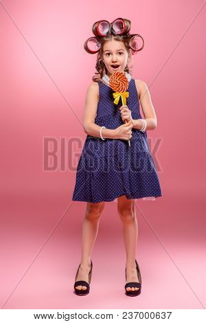 Portrait of a pin-up little girl with curlers in her hair in mother's shoes and lollipop. Studio shot over pink background. Kid's fashion.