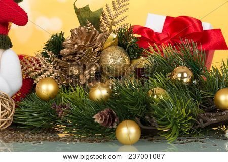 Pine Branch Embellished Golden Christmas Balls, Souvenir Statuette, And Box With Gift On Yellow Back