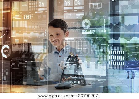 Diligent Boy. Cheerful Clever Little Boy Smiling And Looking Attentively At The Screen Of A Modern L