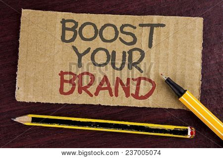 Text sign showing Boost Your Brand. Conceptual photo improve your models name in your field overcome competitors written Cardboard Piece wooden background Led Pen and Pencil next to it. poster