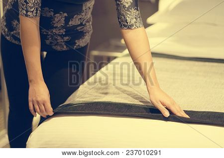 Maid Making Bed In Hotel Room. Toning