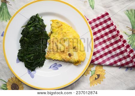 Slice Of Potato Omelet With Side-dish Spinaches In A Dish