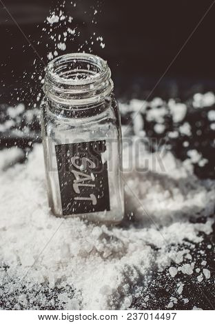 Sprinkled Salt Shakers Of White Salt On The Black Background