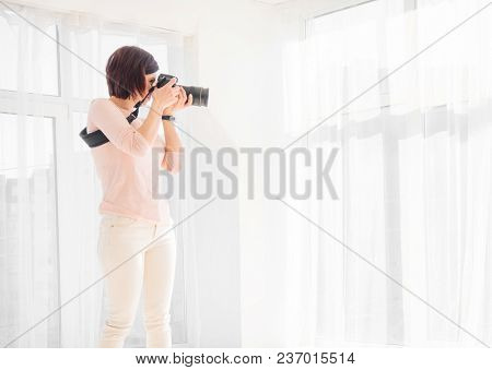 Young woman photographer working in studio. Proffessional female photographer shooting at studio. Girl taking a photo with a professional digital camera