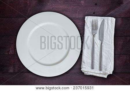 Empty Plate And Silverware On Mahogany Wood.