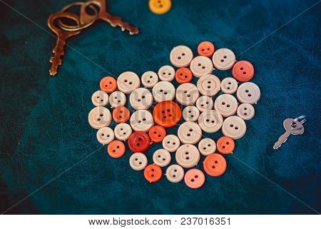 Sewing Buttons In The Shape Of A Heart With Vintage Keys On A Retro Blue Background