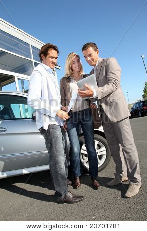 Car seller with couple looking at electronic tablet