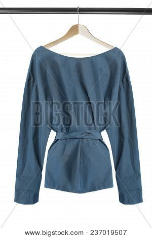 Blue Cotton Blouse Hanging On Wooden Clothes Rack Isolated Over White