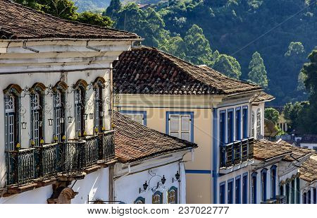 Facade Of Old Houses Built In Colonial Architecture With Their Balconies, Roofs And Colorful Details
