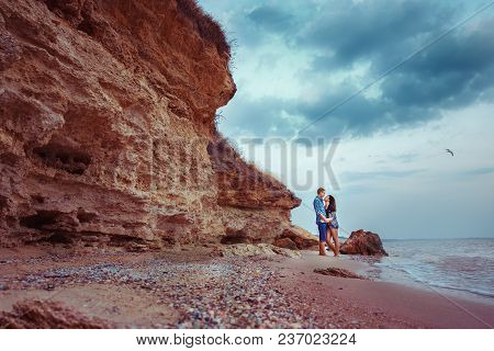 Couple Walking On Beach, Embracing Love. Rock. Bird In The Sky.