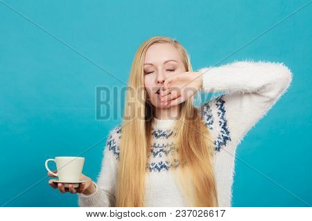 Addiction and caffeine need concept. Sleepy yawning blonde woman holding cup of coffee about to drink it. poster