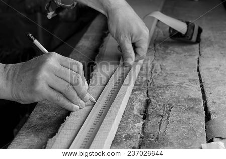 Carpenter Measuring An Oak Board, Marking With  Pencil On Old Cracked Oak Work Bench In Black And Wh