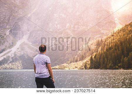A Lonely Elderly Already Balding Man Looks At A Blue Lake Among The Tatra Mountains At Sunset, Morsk