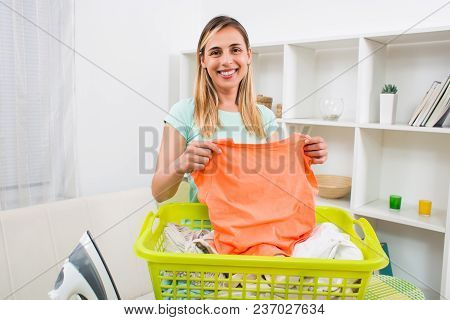 Beautiful Woman With Clothes In Basket And Iron At Her Home.