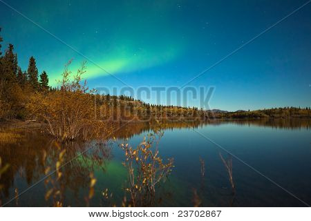Northern lights and fall colors at calm lake