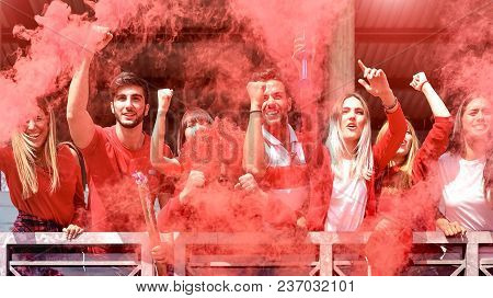 Young Football Supporter Fans Cheering With Colored Smoke Watching Soccer Match Together At Stadium