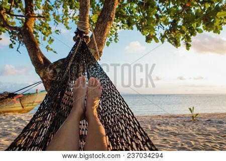Feet Of A Young Woman In Hammock On The Beach Under The Tree
