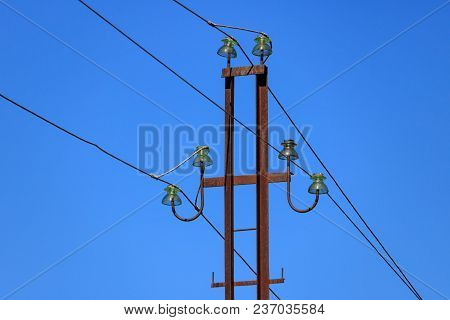 Rusty Metal Power Line Support With Wires And Glass Insulators Close-up Against The Blue Sky
