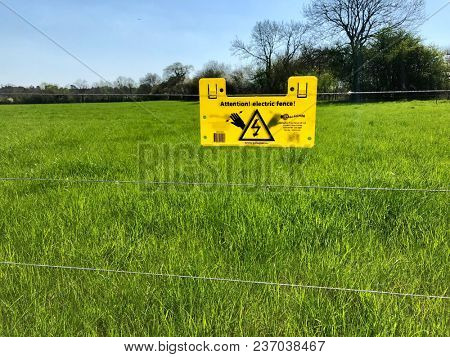 READING, UK - APRIL 19, 2018: Livestock control electric fence and warning sign in Reading, Berkshire, UK.