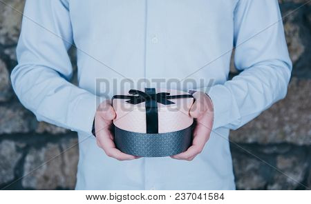 Male Hands Holding A Gift Against Rustic Background.