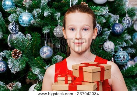 Cute joyful kid girl holding gift boxes on the background of a Christmas tree.