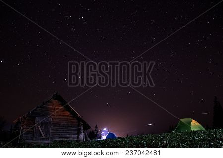 Night Mountain Landscape With Illuminated Tent. Wooden House And Starry Sky Carpathians