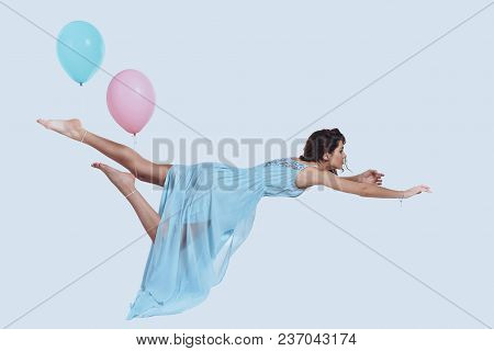 Beauty In Mid-air. Studio Shot Of Attractive Young Woman In Elegant Dress Keeping Arms Outstretched
