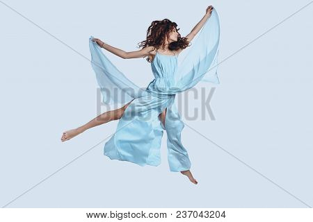 Feeling Free To Do Anything. Full Length Studio Shot Of Attractive Young Woman In Elegant Dress Keep