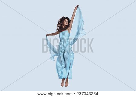 Pure Perfection. Full Length Studio Shot Of Attractive Young Woman In Elegant Dress Looking Away Whi