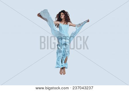 Flying High.... Full Length Studio Shot Of Attractive Young Woman In Elegant Dress Gesturing While H